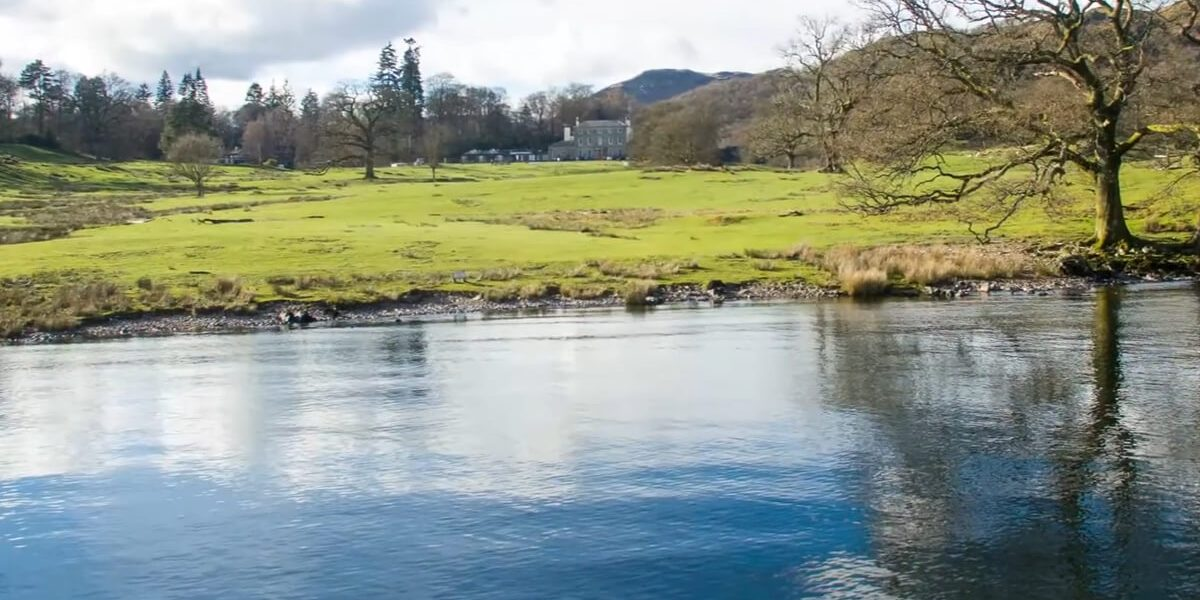 brathay hall with grass and water